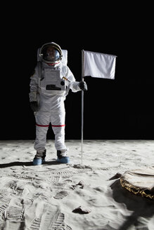 An astronaut standing next to a white flag - FSIF02765
