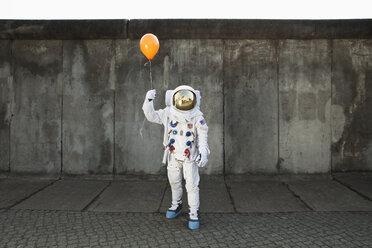 An astronaut on a city sidewalk holding a balloon - FSIF02768