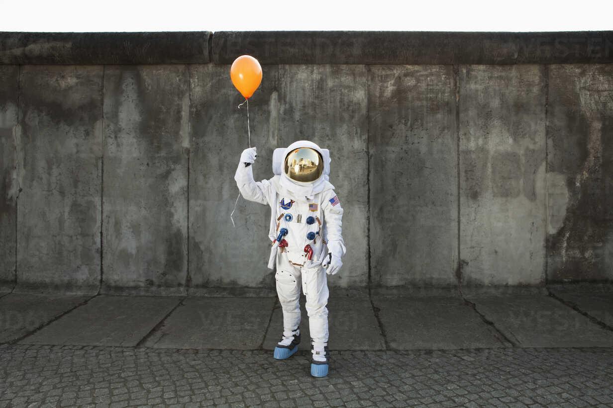 An astronaut on a city sidewalk holding a balloon - FSIF02768 - fStop/Westend61