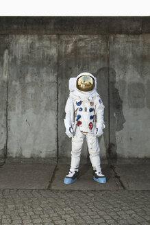 An astronaut standing on a sidewalk in a city - FSIF02771