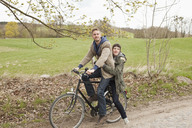 A man giving a ride to his girlfriend on a bicycle in the country - FSIF02777