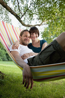 A young happy couple lying in a hammock together - FSIF02792