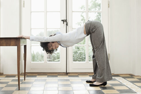 A businesswoman stretching against a table - FSIF02807