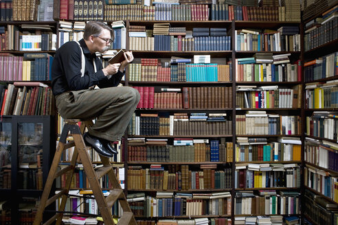 A man sitting on a ladder in a bookstore reading a book - FSIF02813