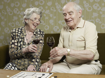 Senior couple drinking red wine make a toast on the couch - FSIF02884