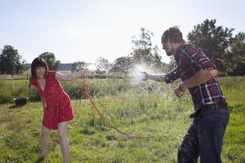 Man and woman spray each other with water in field - FSIF02896