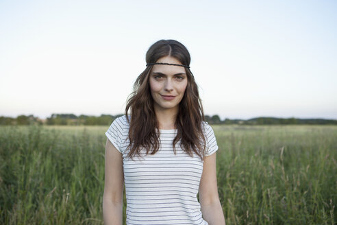 Profile of girl with hair band standing in secluded field - FSIF02908