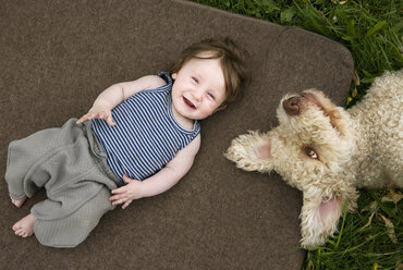 A baby girl and dog lying outside - FSIF02914