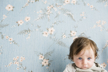 Portrait of a baby in front of floral wallpaper - FSIF02917