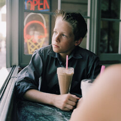 A serious teenage boy with a milkshake looking out a window - FSIF02944