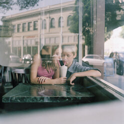 A young teenage couple sharing a milkshake at a diner, viewed through window - FSIF02950
