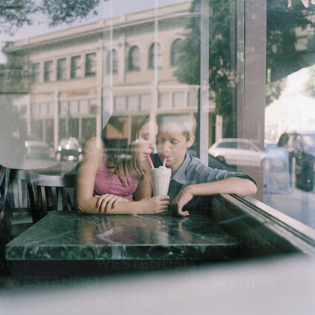 A young teenage couple sharing a milkshake at a diner, viewed through window - FSIF02950 - fStop/Westend61