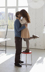 A young woman on a stool kissing her tall boyfriend - FSIF02959