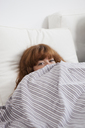 A woman peeking from behind a duvet in bed - FSIF02965