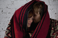 An affectionate couple wrapped in a blanket - FSIF02968