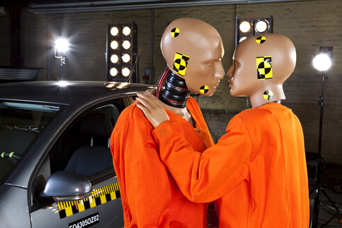Two crash test dummies next to a car in a crash test laboratory about to kiss - FSIF03007