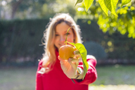 Young woman holding mandarin in a garden - AFVF00193
