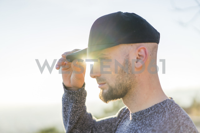 Young man wearing a cap in backlight - AFVF00204
