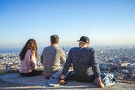 Spain, Barcelona, three friends sitting on a wall overlooking the city - AFVF00216