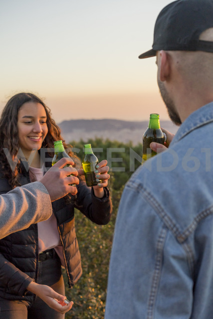 Happy friends clinking beer bottles outdoors at sunset - AFVF00219