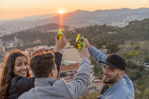 Spain, Barcelona, three happy friends with beer bottles on a hill overlooking the city at sunset - AFVF00222