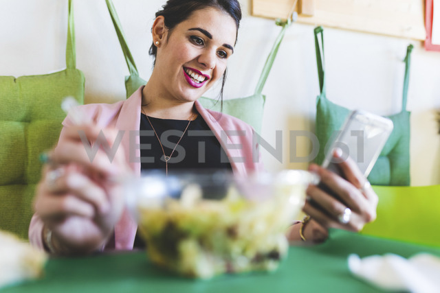 Young businesswoman having healthy lunch and using cell phone - WPEF00130