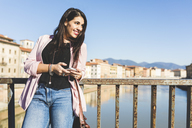 Young businesswoman with smartphone on a bridge in the city - WPEF00136