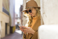 Fashionable young woman in a lane using cell phone - AFVF00234