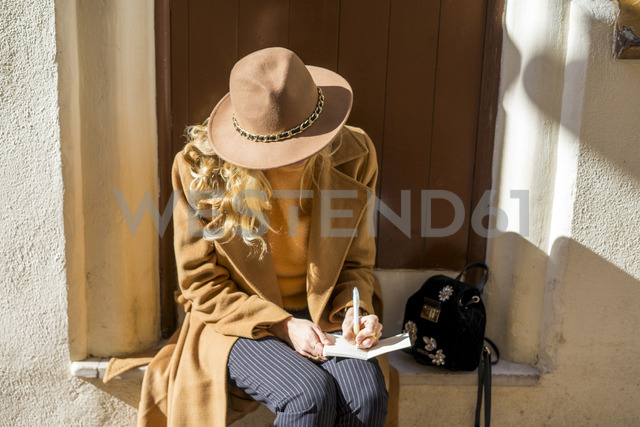 Fashionable young woman sitting at house entrance writing in notebook - AFVF00240