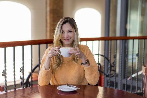 Portrait of smiling young woman in a cafe enjoying a coffee - AFVF00243