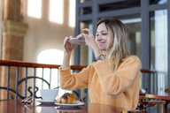 Smiling young woman in a cafe taking cell phone picture - AFVF00246
