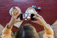 Overhead view of woman in a cafe taking cell phone picture - AFVF00249