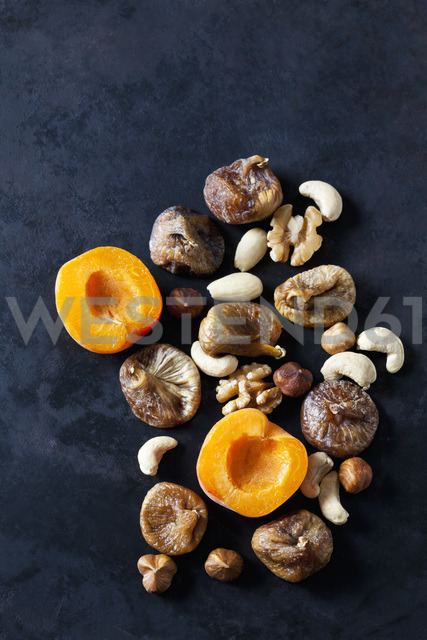 Sliced apricot, dried figs, almonds and various nuts on dark ground - CSF28937