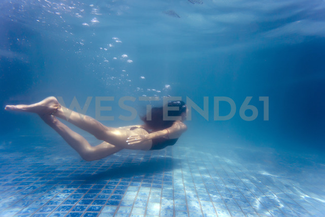 Young woman underwater in a swimming pool - KNTF00987