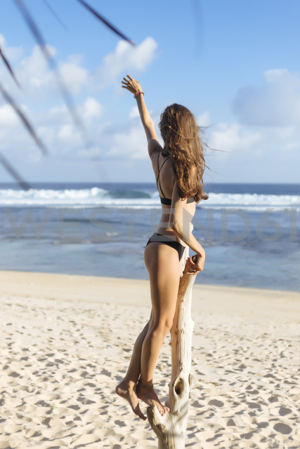 Indonesia, Bali, young woman standing on dead tree on the beach - KNTF00993