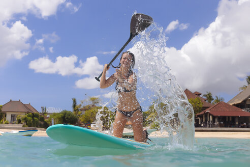 Happy young woman with paddle on surfboard splashing water - KNTF00999