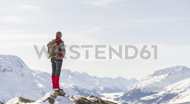 Switzerland, Engadin, hiker in mountainscape looking at view - MRAF00260