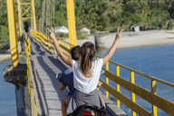 Indonesia, Bali, Lembongan island, carefree young couple riding motor scooter on a bridge - KNTF01000