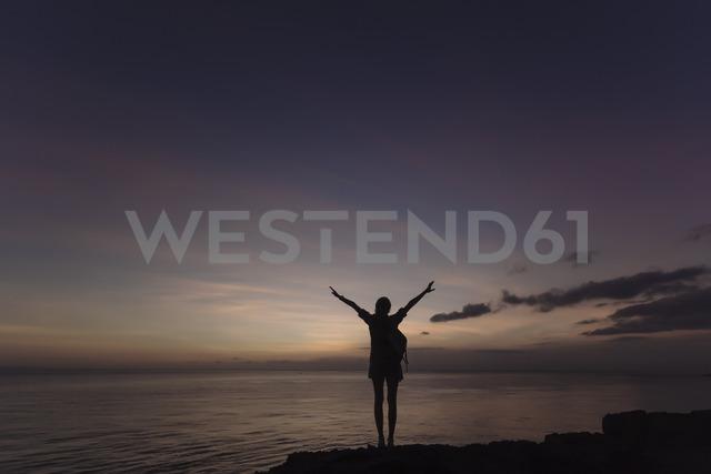 Indonesia, Bali, Lembongan island, young woman at ocean coast at dusk - KNTF01009