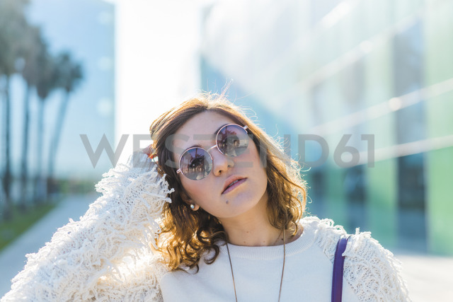 Portrait of young woman wearing sunglasses outdoors - AFVF00250