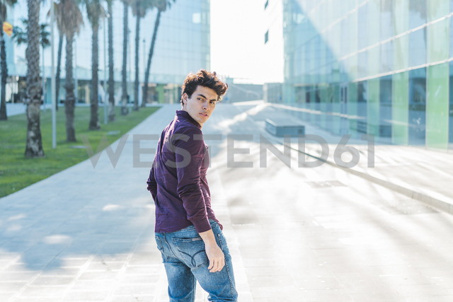 Serious young man walking in the city turning round - AFVF00253