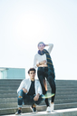 Portrait of stylish young couple on stairs outdoors - AFVF00256
