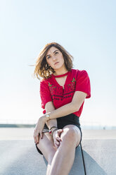 Portrait of serious young woman sitting outdoors - AFVF00262