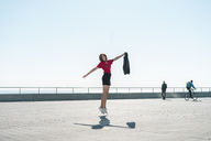 Fashionable young woman jumping on waterfront promenade - AFVF00268