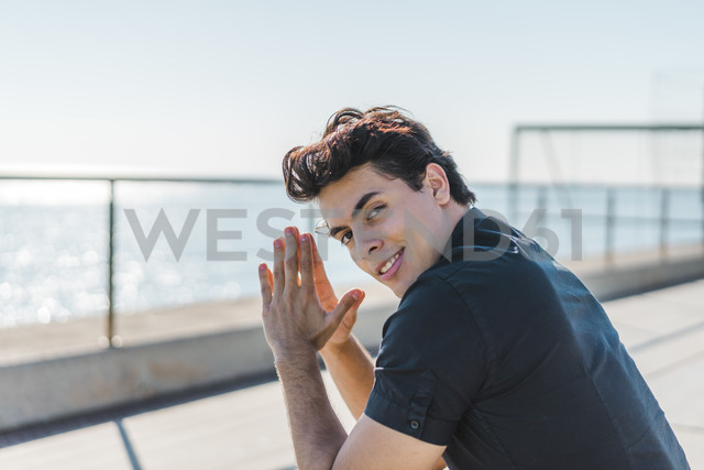 Portrait of smiling young man at the coast - AFVF00271