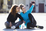 Two smiling sportive young women having a break taking a selfie - JSRF00005
