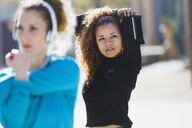 Two focused sportive young women stretching listening to music - JSRF00008