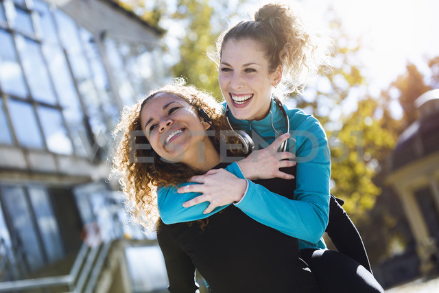 Happy young woman carrying friend piggyback - JSRF00011
