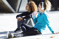 Two sportive young women having a break listening to music - JSRF00014