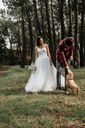 Bride and groom in forest with funny dog-shaped balloon - DAPF00891